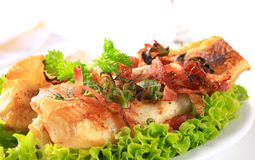 Pan fried fish fillets with bacon bits Royalty Free Stock Photo