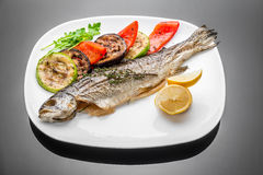 Pan fried grilled roasted cooked whole fish trout sea bass salmon cod. Salad lemon white plate royalty free stock images