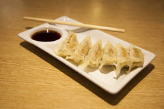 Pan fried gyoza dumplings with a dip sauce Royalty Free Stock Images