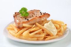 Pan fried pork chop with fries Royalty Free Stock Image