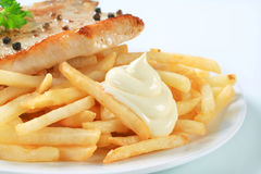 Pan fried pork chop with fries Stock Images
