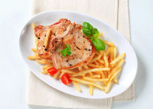 Pan fried pork chop with fries Royalty Free Stock Photography