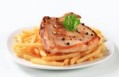 Pan fried pork chop with fries Stock Photos