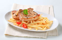 Pan fried pork chops with fries Stock Photography