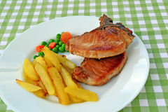 Pan-fried pork steak with french fries. Pan-fried pork steaks well done, with chips and garden peas royalty free stock photos