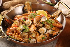 Pan of fried rice with clams, oysters and shrimps royalty free stock images