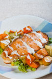 Fried salmon on a garden salad topped with fresh butter Stock Images