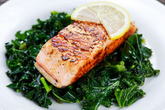 Pan fried Salmon Served with Kale on plate Stock Images