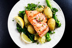 Pan fried Salmon Served with potatoes and tenderstem broccoli. Royalty Free Stock Image