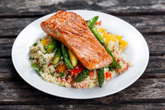 Pan fried salmon with tender asparagus and courgette served on couscous mixed with sweet tomato, yellow pepper salsa. Royalty Free Stock Images