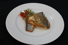 Pan fried sea bass in a white plate royalty free stock images