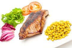 Pan fried steak, green peas and vegetables Royalty Free Stock Photos