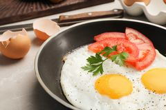 Pan with fried sunny side up eggs and tomato. On table, closeup stock photography