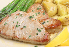 Pan-Fried Tuna Steaks. With asparagus and new potatoes Royalty Free Stock Images