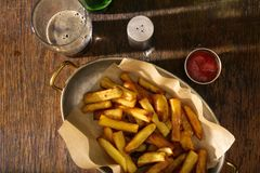 Pan of fries with ketchup and glass of dark beer Stock Photos