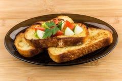 Pan frito con las rebanadas de tomates y de pepinos en plato Fotografía de archivo libre de regalías