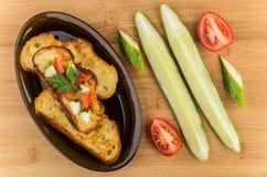 Pan frito con los tomates y los pepinos en plato en la tabla Foto de archivo