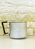 Pan in front of a white bricks wall. Old Pan in front of a dirty white bricks wall Royalty Free Stock Photo