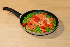 Pan full of salmon steacks, peas, tomatoes and capers Royalty Free Stock Image