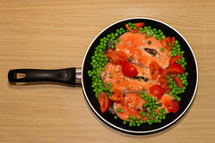 Pan full of salmon steacks, peas, tomatoes and capers Stock Image