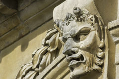 Pan gargoyle feature. Classic Pan, or the devil, gargoyle feature carved in stone Stock Image