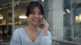 Pan geschossene Zeitlupe der asiatischen weiblichen lachenden Unterhaltung am Telefon beim Gehen stock video