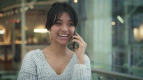Pan geschossene Zeitlupe der asiatischen weiblichen lachenden Unterhaltung am Telefon beim Gehen stock footage