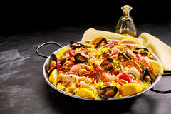 Pan of gourmet paella with shrimp and mussels. Garnished with fresh lemon slices and served with oil or dressing in a decanter, with copy space Stock Images