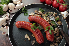 Pan with grilled sausages with mushrooms Stock Photography