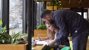 PAN of guy and girl together reading a textbook in a cafe.  stock footage