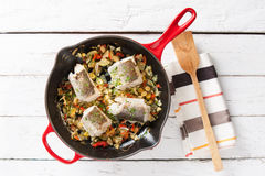 Pan of hake and vegetables. Hake and vegetables in a pan on a white table overhead shot Royalty Free Stock Image