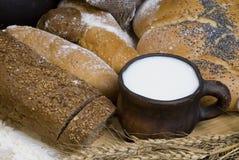 Pan, harina, cereales y una taza de leche. Imagenes de archivo