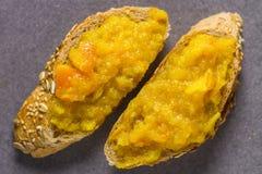Pan hecho en casa con el atasco anaranjado de la fruta cítrica en Gray Grey Marble Background foto de archivo