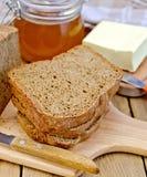 Pan hecho en casa de Rye con la miel y la mantequilla a bordo Fotos de archivo libres de regalías