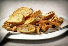Pan hecho en casa de Taralli y de Focaccia en la placa blanca Foto de archivo libre de regalías
