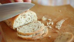 Pan hecho en casa que corta sobre rebanadas finas usando el cuchillo afilado almacen de video