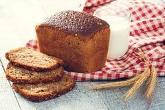 Pan hecho en casa y leche con las espiguillas del trigo en un paño en tableros Foto de archivo libre de regalías