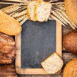 Pan hecho en casa y trigo en la tabla de madera Foto de archivo libre de regalías