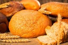 Pan hecho en casa y trigo en la tabla de madera Fotos de archivo libres de regalías