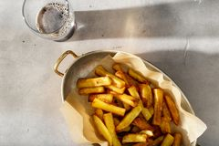 Pan of homemade french fries with glass of dark beer Royalty Free Stock Photos