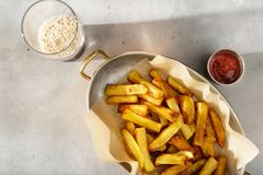Pan of homemade french fries with ketchup and dark beer Royalty Free Stock Images