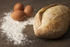 Pan, huevos y harina en una sobremesa de madera imagen de archivo libre de regalías