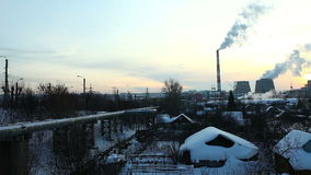Pan on industrial view at sunset  in winter. Thermal station smoke in sky at winter sunset in Russia stock video