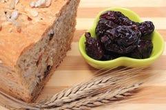 Pan integral cocido, ciruelos secados y oídos del trigo Fotos de archivo libres de regalías