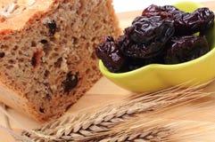 Pan integral cocido, ciruelos secados y oídos del trigo Imagen de archivo libre de regalías
