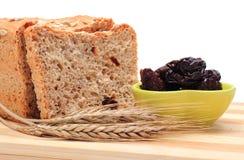 Pan integral cocido, ciruelos secados y oídos del trigo Imagenes de archivo