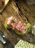 Pan integral con las semillas rematadas con la salchicha y la ensalada italianas picantes del salami en un tablero de madera rúst imágenes de archivo libres de regalías