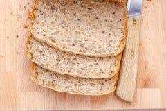 Pan integral cortado en tabla de cortar Imagen de archivo libre de regalías