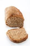 Pan integral de centeno y una rebanada de pan en el tablero de madera Fotografía de archivo