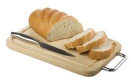 Pan largo rebanado y un cuchillo en una tarjeta de corte Imagen de archivo libre de regalías